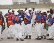 Extractive industry workers are pictured on a beach; a new report recommends that transparency initiatives need to be more inclusive and relevant to local needs for communities most affected by oil, gas or mining projects (Photo: iStockphoto.com/Getty Images)