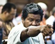 A man points his finger at someone in a meeting room at a debate at a meeting on the sustainable development of the Amazon at Rio+20.