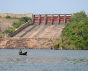 One man in a small boat on a reservoir, in front of a large dam