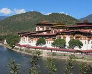 Picture of the Punakha Dzong, an administrative centre in Bhutan. A river runs past it in the foreground and wooded hills rise behind it.
