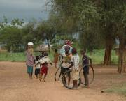 Children stand on a dirt road in a village in Burkina Faso.