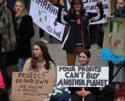 "A group of young women protestors with placards, one reading ""Your profits can't buy another planet"""