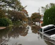 A pick up truck lies mostly submerged under a water in a flooded street.