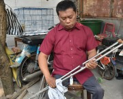 A seated man cleaning a crutch.