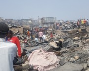 People observe burnt down structures