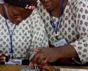 Women working together to build a solar lighting circuit board.
