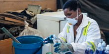 A woman wearing a mask pours chemicals into a bottle.
