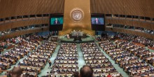 A large audience sits in a cricualr room, facing a man behind a lectern. The UN logo is printed on the wall.