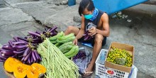 Man sits on the floor holding aubergines. In front, there's a table with vegetables