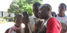 Young people in Okola, Cameroon, cluster around a Global Positioning System that they are using to create a community map with geographical features.