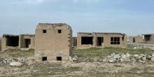 A series of grey abandoned and crumbling stone houses in an unwelcoming landscape