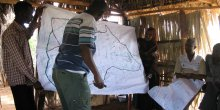 Men present findings on a large map at the front of a community meeting