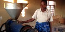 Esther Msafiri demonstrates using electricity for oil pressing in Njombe region, Tanzania (Photo: Sarah Best/IIED)