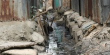 Sewage and water runs down the centre of a makeshift 'drain' surrounded by sandbags and wood