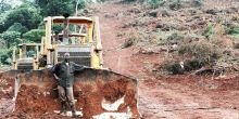 A man in Uganda stands by a digger sitting next to a dirt road.