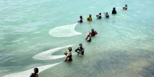 Women fishing in shallow water
