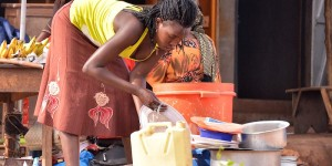 Woman washing dishes with a jerrycan.