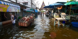 A trader wades through knee-high flooded water in a marketplace