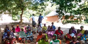 Women at an outside meeting sat on the floor under trees