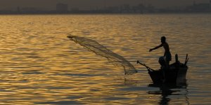 A fisher casting a net from a small boat surrounded by a large expanse of water