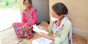 A data collector speaks to a householder.