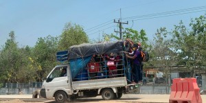 Pick-up van packed with people and suitcases.