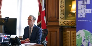 Man sitting on a desk in front of a computer, with the Union flag behind him