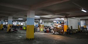 Relocated street vendors operate in the car park below the alun-alun of the Masjid Raya Mosque in Bandung, but this basement area does not attract many customers and vendors have to breathe in car and motorcycle fumes due to the poor air circulation (Photo: Kemal Jufri/Panos Pictures)