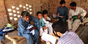 Researchers talk to villagers in Sheikhuwal village in rural Pakistan