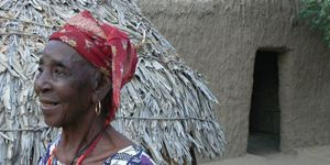 Old woman in profile in front of thatched hut and mud house. Niger.