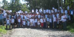 A community in the Philippines protesting against a mining project in their area holds up their resolutions against the plans, developed through the support of paralegals who provided them with legal advice