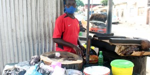 A mask-wearing man stands behind a food stall
