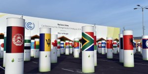 Flags of countries around the world adorn pylons outside a conference venue