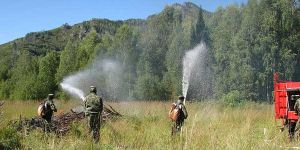 Men spray water from water hoses onto a small fire in Kazakhstan