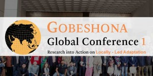 "A group of people pose for a picture, behind words that say ""Gobeshona Global Conference 1"""