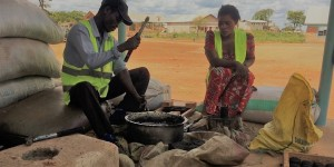 A man and woman sat down cooking with a charcoal cookstove.