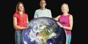 Three people stand around a large planet Earth globe