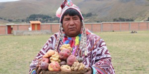 Man wearing traditional clothing holds a plate with potatoes.