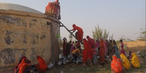 A group of women use a ladder to climb up to an imposing well to collect water in a desert-like landscape