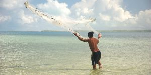 An image of an artisanal fisher in Kiribati casting his net into the water; 90 per cent of all fishers are small-scale or artisanal (Photo: Quentin Hanich/WorldFish, Creative Commons, via Flickr)