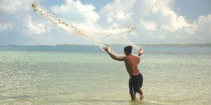 A Kiribati fisherman throws a net