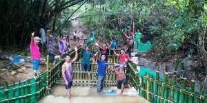 Men posing for a photo while constructing a weir with bamboo structures.