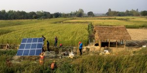 People installing solar panels in a field