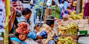 Women sell bananas at stalls at a market