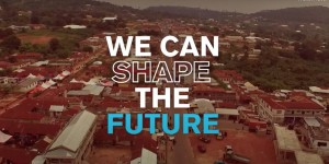 Aerial view of city with overlay text: we can shape the future