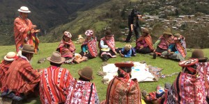 People wearing traditional clothing sit in a circle in a field.