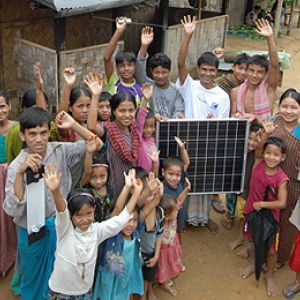 An image of villagers in a remote village in northern Bangladesh proudly displaying their first solar panel, purchased with a micro loan. Bangladesh aspires to be one of the world's largest solar providers (Photo: ILO in Asia and the Pacific, Creative Commons, via Flickr)