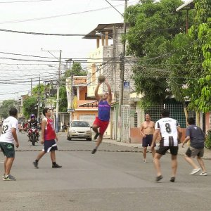 A group of young men play volleyball in the middle of the street, with a makeshift net