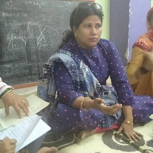 Three women sit on the floor for a meeting