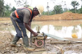A miner concentrates as he adjusts a water pump